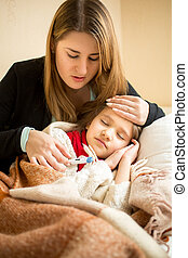 young mother hugging sick girl in bed