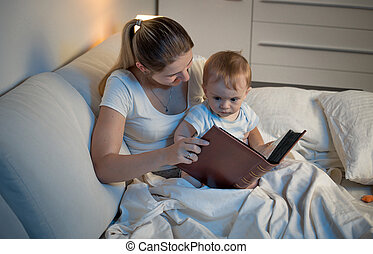 Portrait of young mother reading book to her baby son before going to sleep