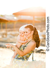 Portrait of young mother with baby on beach showing something by pointing in corner