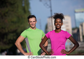 portrait of young multietnic jogging couple ready to run on...