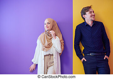 portrait of young muslim couple isolated on colorful background