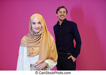 portrait of young muslim couple isolated on pink background