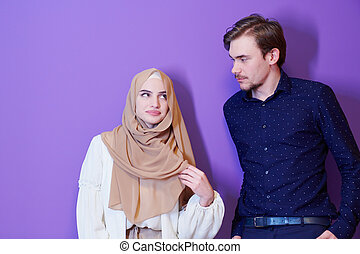 portrait of young muslim couple isolated on purple background