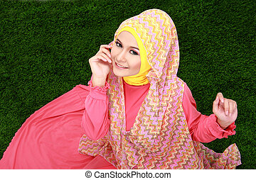 Portrait of young muslim girl wearing hijab sitting on grass...
