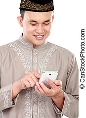 young muslim man typing on his smartphone - portrait of...