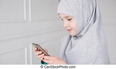 Portrait of young muslim teen girl in grey hijab is playing...