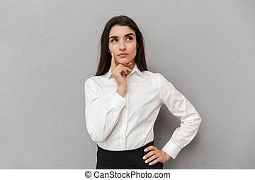 Portrait of young office woman with brooding look in white shirt seriously looking aside and holding finger at cheek, isolated over gray background