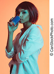 portrait of young pensive african american woman drinking from can