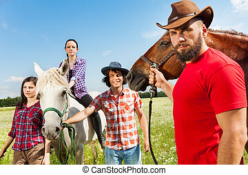 Portrait of young people and their horses in field