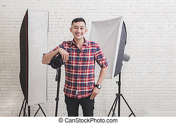 Young photographer with camera in professionally equipped studio