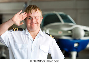 Portrait of young pilot with down syndrome in hangar. -...