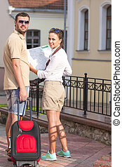 Portrait of Young Positive Caucasian Couple Travelling with Trolley Suitcase Outdoors. Posing With Map and Camera.