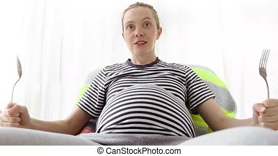 Portrait of young pregnant woman, stomach in focus -...