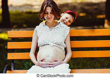 Portrait of young pregnant woman with her son