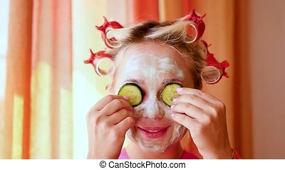 portrait of young pretty woman in robe with cosmetic face mask.