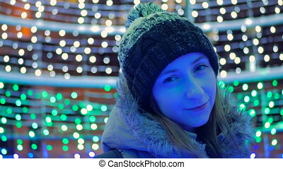 Portrait of young pretty woman in the city at night