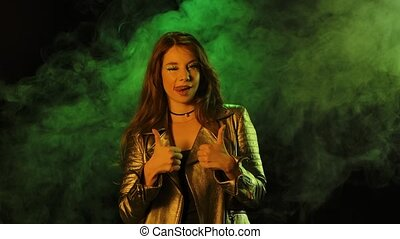 Portrait of young pretty woman looking at the camera shows ok gesture, thumb up and thumb down. Brunette with shiny eye makeup in a silver jacket posing against a smoky studio background backlit by green neon lights. Close up. Slow motion.