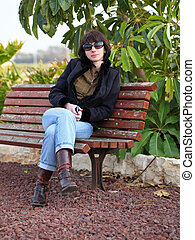 Portrait of young pretty woman sitting on bench at autumn park