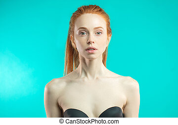 Portrait of young red-haired woman wearing black lingerie looking at camera.
