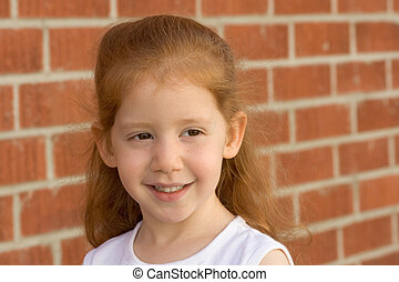 Portrait of Young redhead kid girl by brick wall