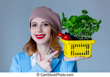 woman in coat and beret with basket of herbs