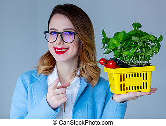 woman in coat with basket of herbs