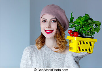 woman in sweater and beret with basket of herbs