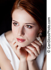 Portrait of young redhead woman with breautiful earrings