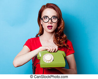 Portrait of young redhead woman with handset