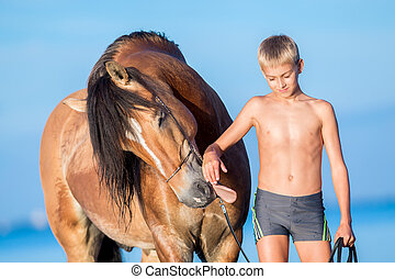 Portrait of young rider with horse in sunset.