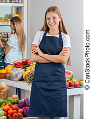 Portrait of young saleswoman standing arms crossed with woman shopping in background