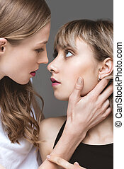 portrait of young sensual lesbian couple emracing and...
