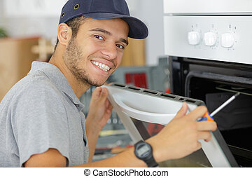 portrait of young serviceman fitting electric oven