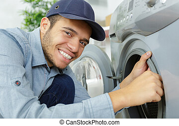 portrait of young serviceman working on washing machine