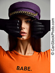 Portrait of young sexy brunette woman in purple peaked cap or beret with gold chain in leather gloves and orange shirt