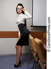 portrait of young sexy business woman in an office with glasses red lips