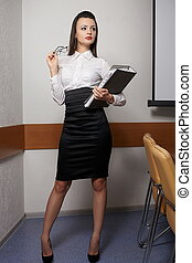 portrait of young sexy business woman in an office with glasses red lips with documents