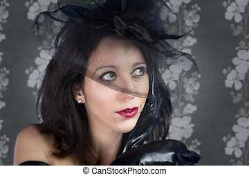 Portrait of young sexy woman in black veil on vintage background