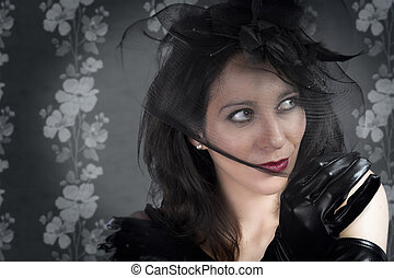 Portrait of young sexy woman in black veil on vintage wall