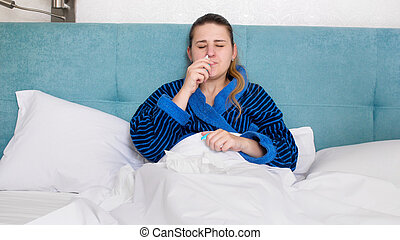 Portrait of young sick woman with runny nose using nasal spray