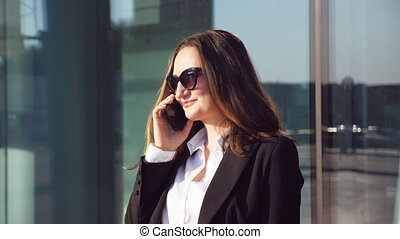 Portrait of young smiling businesswoman talking on phone....
