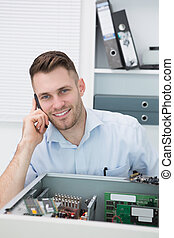 Portrait of young smiling computer engineer on call in front of open cpu at workplace