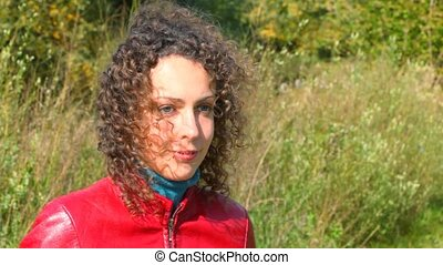 portrait of young smiling curly-headed woman against fluttering grass