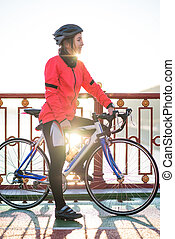 Portrait of Young Smiling Female Cyclist in Orange Jacket Resting with Road Bicycle in the Cold Sunny Autumn Day