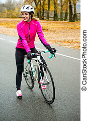 Portrait of Young Smiling Female Cyclist in Pink Jacket Resting with Road Bicycle in the Cold Sunny Autumn Day