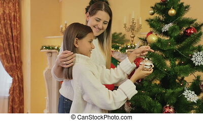 Portrait of young smiling mother with daughter decorating Christmas tree at living room