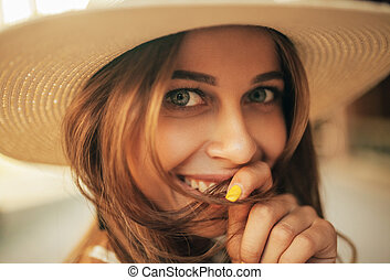 Portrait of young smiling woman in hat.