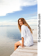 Young smiling woman in white clothes on a pier