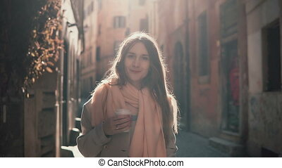 Portrait of young smiling woman looking at camera. Happy attractive girl standing in morning street, doing up hair.