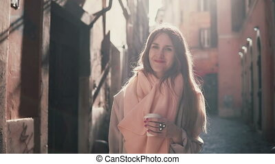 Portrait of young smiling woman looking at camera. Happy brunette girl standing in morning street and drinking coffee.